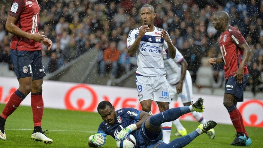 Lille's Nigerian goalkeeper Vincent Enyeama (C, bottom) blocks a shot on goal by Lyon's French forward Claudio Beauvue (back) during the French L1 football match between Lyon and Lille at the Gerland stadium in Lyon, eastern France, on September 12, 2015. AFP PHOTO / ROMAIN LAFABREGUE (Photo credit should read ROMAIN LAFABREGUE/AFP/Getty Images)