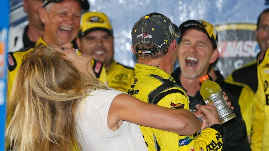 Matt Kenseth, center, gets as hug from his wife, Katie, after his win in the NASCAR Sprint Cup auto race at Richmond International Raceway in Richmond, Va., Saturday, Sept. 12, 2015. (AP Photo/Steve Helber)