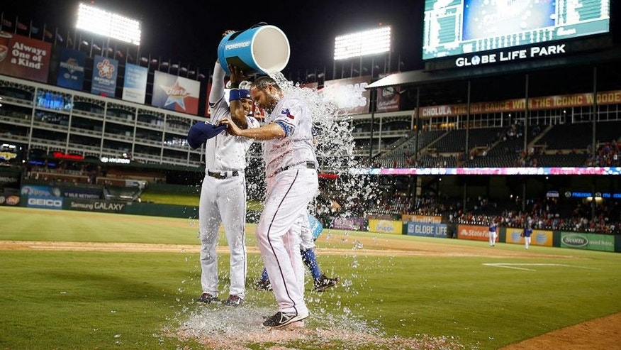 Sep 11, 2015; Arlington, TX, USA; Texas Rangers starting pitcher Colby Lewis (48) has water dumped on him by shortstop Elvis Andrus (1) after winning the game against the Oakland Athletics at Globe Life Park in Arlington. Texas won 4-0. Mandatory Credit: Tim Heitman-USA TODAY Sports