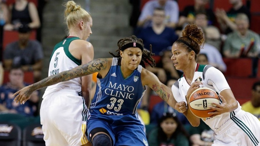 <p>Minnesota Lynx's Seimone Augustus (33) defends between Seattle Storm's Alysha Clark, right, and Abby Bishop during the first half of a WNBA basketball game Thursday, June 25, 2015, in Seattle. (AP Photo/Elaine Thompson)</p>