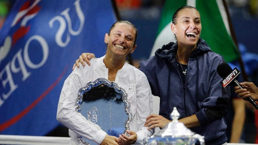 Roberta Vinci, of Italy, left, and Flavia Pennetta, of Italy, react during the trophy ceremony for the women's championship match of the U.S. Open tennis tournament, Saturday, Sept. 12, 2015, in New York. Pennetta beat Vinci in straight sets. (AP Photo/David Goldman)