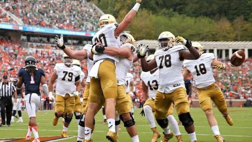CHARLOTTESVILLE, VA - SEPTEMBER 12: Tight end Durham Smythe #80 of the Notre Dame Fighting Irish celebrates with teammates after scoring a touchdown on a fake field goal attempt in the first quarter against the Virginia Cavaliers at Scott Stadium on September 12, 2015 in Charlottesville, Virginia. (Photo by Patrick Smith/Getty Images)