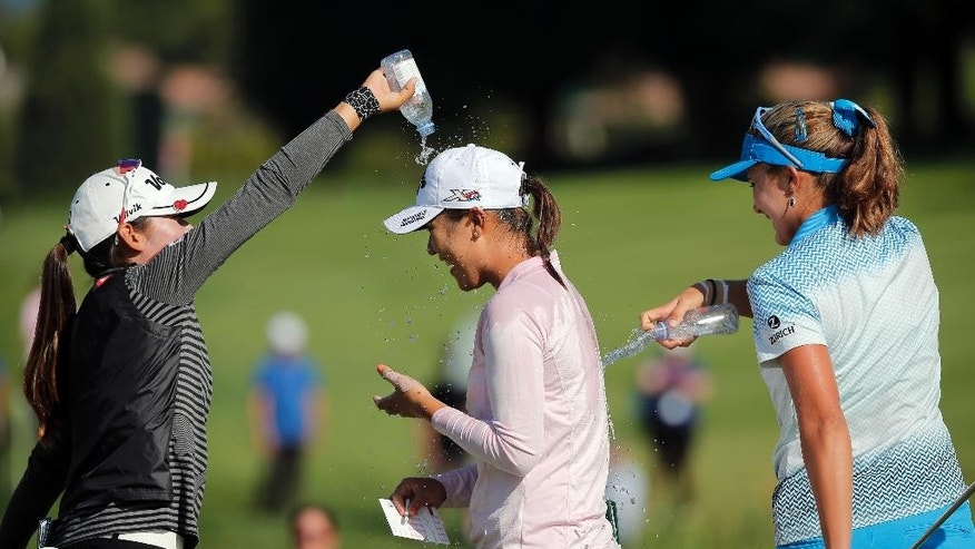 Lydia Ko of New Zealand, center, celebrates with Mi Hyang Lee of South Korea, left, and Lexi Thompson of the U.S, right, after winning the Evian Championship women's golf tournament in Evian, eastern France, Sunday, Sept. 13, 2015. (AP Photo/Laurent Cipriani)