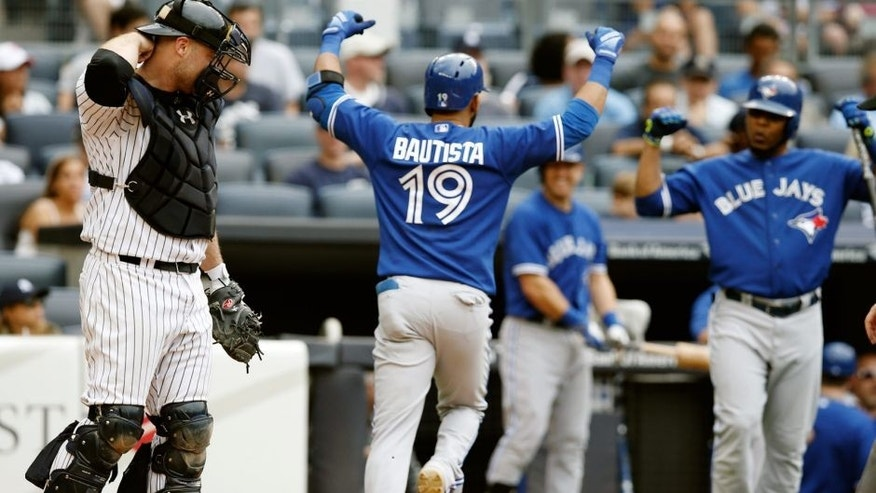 New York Yankees catcher Brian McCann, left, reacts as Toronto Blue Jays Jose Bautista (19) celebrates heading to the dugout after hitting an eighth-inning, solo, home run as on-deck-batter Edwin Encarnacion right, joins the celebration during the first baseball game of a doubleheader at Yankee Stadium in New York, Saturday, Sept. 12, 2015. (AP Photo/Kathy Willens)