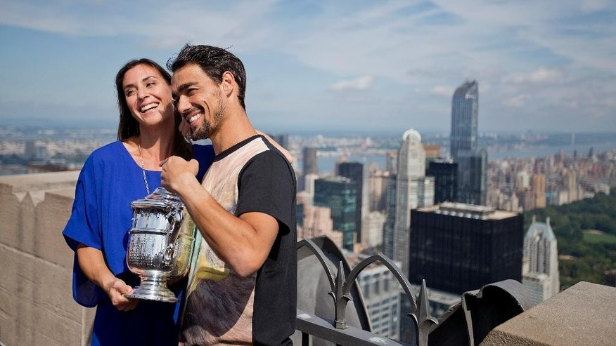 Flavia Pennetta, of Italy, left, poses with her fiance and fellow tennis player Fabio Fognini with the U.S. Open tennis women's singles championship trophy during a visit to the Top of the Rock Observation Deck at Rockefeller Center, Sunday, Sept. 13, 2015, in New York. (AP Photo/David Goldman)