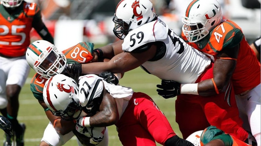 Oct 11, 2014; Miami Gardens, FL, USA; Cincinnati Bearcats running back Mike Boone (27) is tackled by Miami Hurricanes linebacker Darrion Owens (58) in the second half at Sun Life Stadium. The Hurricanes won 55-34. Mandatory Credit: Robert Mayer-USA TODAY Sports