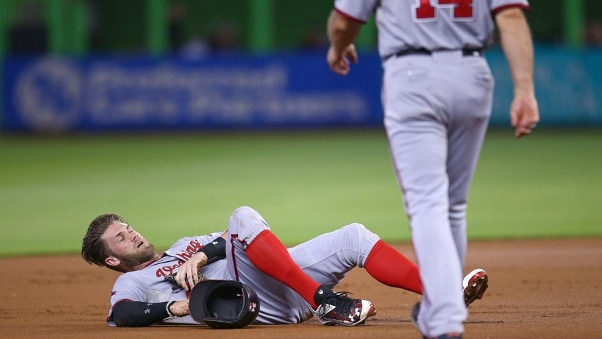 MIAMI, FL - SEPTEMBER 13: Bryce Harper #34 of the Washington Nationals lays injured on the infield after colliding with Miguel Rojas of the Miami Marlins during the first inning of the game at Marlins Park on September 13, 2015 in Miami, Florida. Harper was taken out of the game after the injury. (Photo by Rob Foldy/Getty Images)