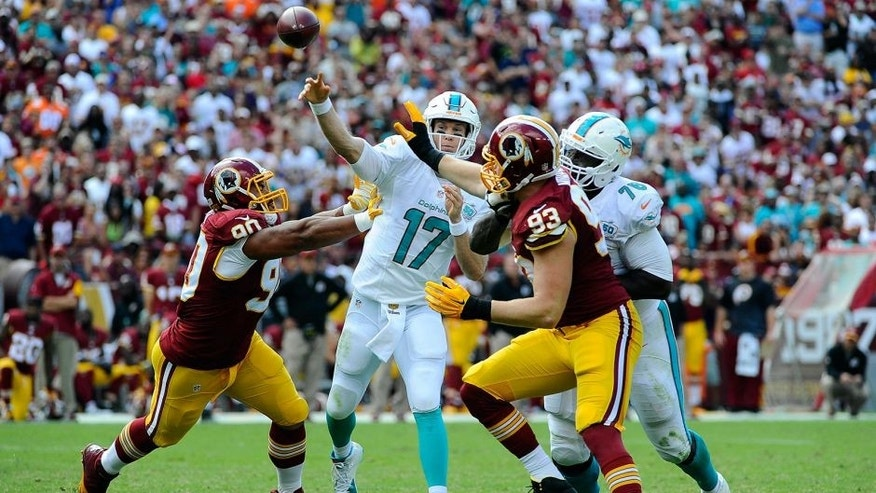 Sep 13, 2015; Landover, MD, USA; Miami Dolphins quarterback Ryan Tannehill (17) attempts a pass as Washington Redskins defensive end Stephen Paea (90) and outside linebacker Trent Murphy (93) pressure during the second half at FedEx Field. Mandatory Credit: Brad Mills-USA TODAY Sports