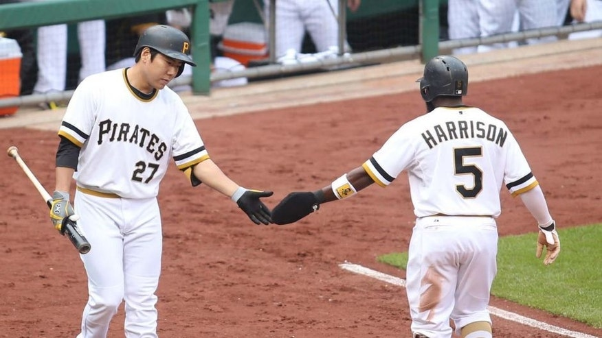 Pittsburgh Pirates third baseman Jung Ho Kang greets left fielder Josh Harrison after Harrison scored a run against the Milwaukee Brewers at PNC Park in Pittsburgh on Sunday, Sept. 13, 2015.