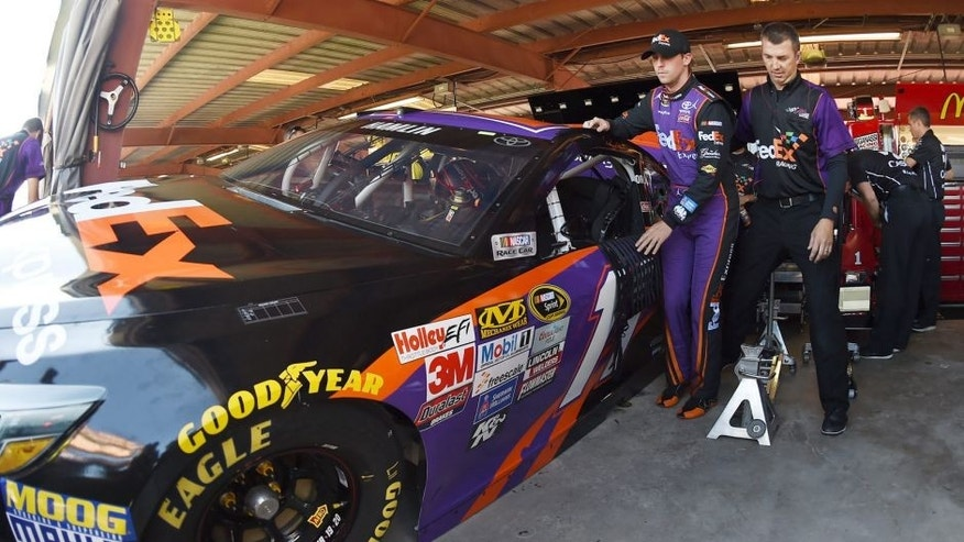 RICHMOND, VA - SEPTEMBER 11: A crew member helps Denny Hamlin, driver of the #11 FedEx Express Toyota, climb into his car during practice for the NASCAR Sprint Cup Series Federated Auto Parts 400 at Richmond International Raceway on September 11, 2015 in Richmond, Virginia. (Photo by Rainier Ehrhardt/NASCAR via Getty Images)
