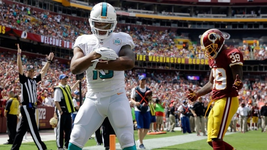 Miami Dolphins wide receiver Rishard Matthews (18) celebrates in front of Washington Redskins cornerback David Amerson (39) after making a touchdown during the first half of an NFL football game Sunday, Sept. 13, 2015, in Landover, Md. (AP Photo/Patrick Semansky)