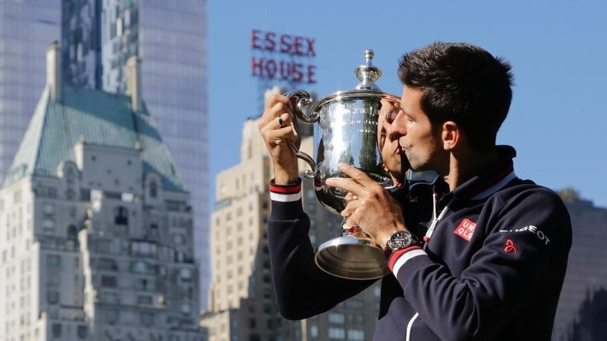 Novak Djokovic poses with the U.S. Open tennis championship trophy, Monday, Sept. 14, 2015, in New York's Central Park. Djokovic defeated Roger Federer 6-4, 5-7, 6-4, 6-4 on Sunday, to earn his second U.S. Open title, third major championship of the year and 10th Grand Slam trophy in all. (AP Photo/Mark Lennihan)