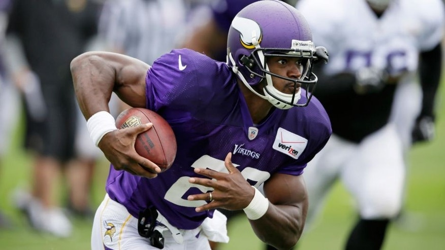 <p>Minnesota Vikings running back Adrian Peterson runs up field during NFL football training camp, Sunday, July 27, 2014, in Mankato, Minn. (AP Photo/Charlie Neibergall)</p>