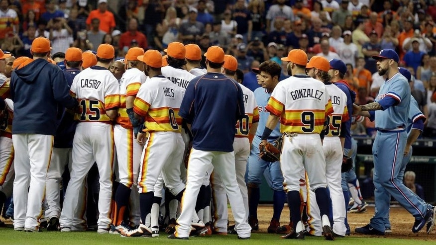 Houston Astros and Texas Rangers benches confront one another after Astros catcher Hank Conger and Rangers' Rougned Odor had words at the plate in the ninth inning of a baseball game Saturday, July 18, 2015, in Houston. Texas won 7-6. (AP Photo/Pat Sullivan)