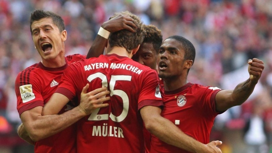 MUNICH, GERMANY - SEPTEMBER 12: Thomas Mueller (2ndL) of Bayern Muenchen celebrates his penalty goal with teammates Robert Lewandowski, David Alaba and Douglas Costa (L-R) during the Bundesliga match between FC Bayern Muenchen and FC Augsburg at Allianz Arena on September 12, 2015 in Munich, Germany. (Photo by Alexandra Beier/Bongarts/Getty Images)
