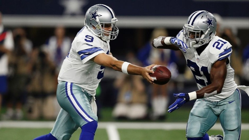 Dallas Cowboys quarterback Tony Romo (9) hands off the ball to running back Joseph Randle (21) during the first half of an NFL football game against the New York Giants, Sunday, Sept. 13, 2015, in Arlington, Texas. (AP Photo/Brandon Wade)