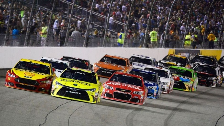 RICHMOND, VA - SEPTEMBER 12: Matt Kenseth, driver of the #20 Dollar General Toyota, and Joey Logano, driver of the #22 Shell Pennzoil Ford, lead the field in a restart during the NASCAR Sprint Cup Series Federated Auto Parts 400 at Richmond International Raceway on September 12, 2015 in Richmond, Virginia. (Photo by Robert Laberge/Getty Images)