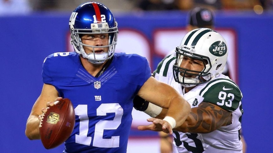 Aug 29, 2015; East Rutherford, NJ, USA; New York Giants quarterback Ryan Nassib (12) avoids New York Jets defensive end Jason Babin (93) during the second half at MetLife Stadium. The Jets defeated the Giants 28-18. Mandatory Credit: Ed Mulholland-USA TODAY Sports