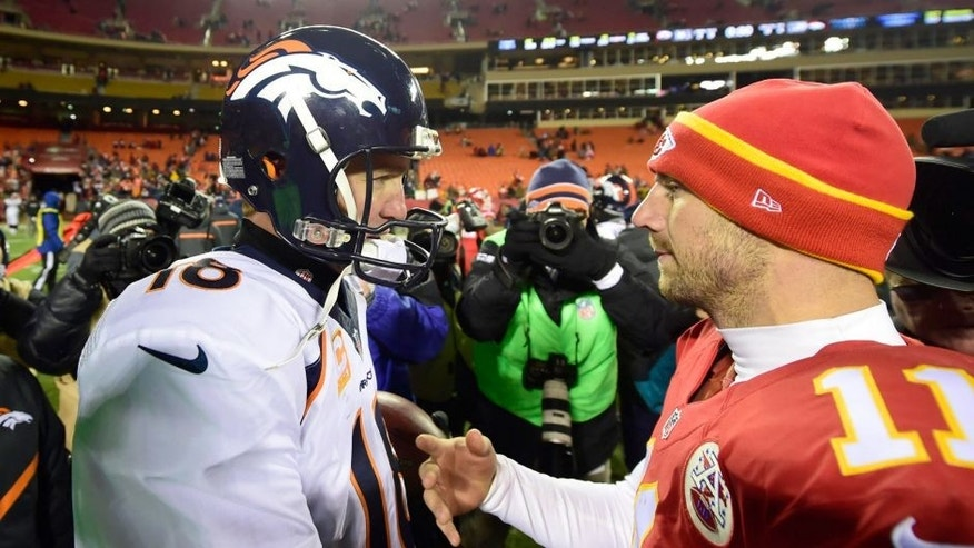 Nov 30, 2014; Kansas City, MO, USA; Denver Broncos quarterback Peyton Manning (18) greets Kansas City Chiefs quarterback Alex Smith (11) following the game at Arrowhead Stadium. The Broncos defeated the Chiefs 29-16. Mandatory Credit: Ron Chenoy-USA TODAY Sports