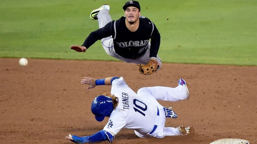 LOS ANGELES, CA - SEPTEMBER 15: Nolan Arenado #28 of the Colorado Rockies makes a throw over Justin Turner #10 of the Los Angeles Dodgers for a double play during the fourth inning at Dodger Stadium on September 15, 2015 in Los Angeles, California. (Photo by Harry How/Getty Images)