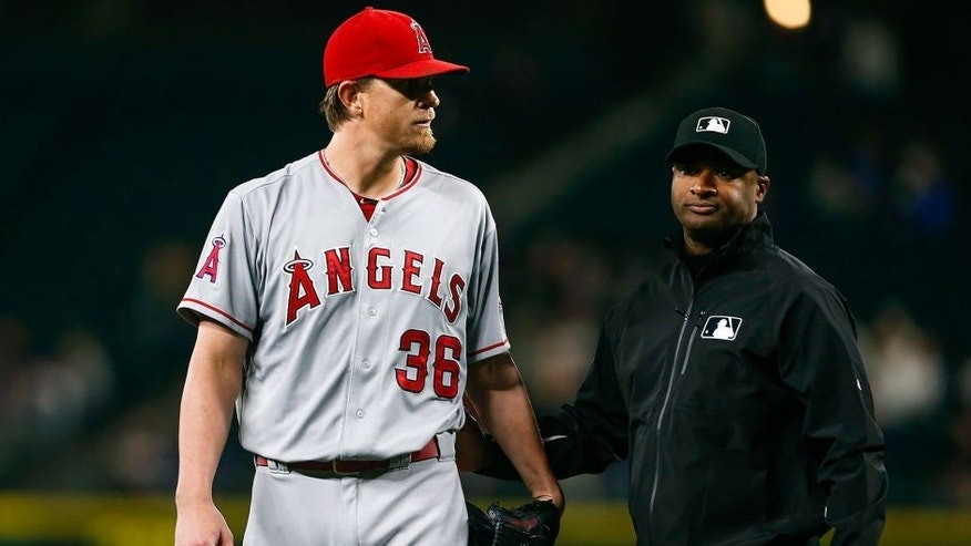 Sep 16, 2015; Seattle, WA, USA; Los Angeles Angels pitcher Jered Weaver (36) is escorted from the mound by umpire Alan Porter (64) after being ejected from the game for hitting Seattle Mariners third baseman Kyle Seager (not pictured) with a pitch during the fifth inning at Safeco Field. Mandatory Credit: Joe Nicholson-USA TODAY Sports