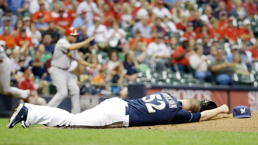 Milwaukee Brewers starting pitcher Jimmy Nelson lays on the ground after being hit in the head by a ball hit by St. Louis Cardinals' Thomas Pham during the third inning of a baseball game Thursday, Sept. 17, 2015, in Milwaukee. (AP Photo/Morry Gash)