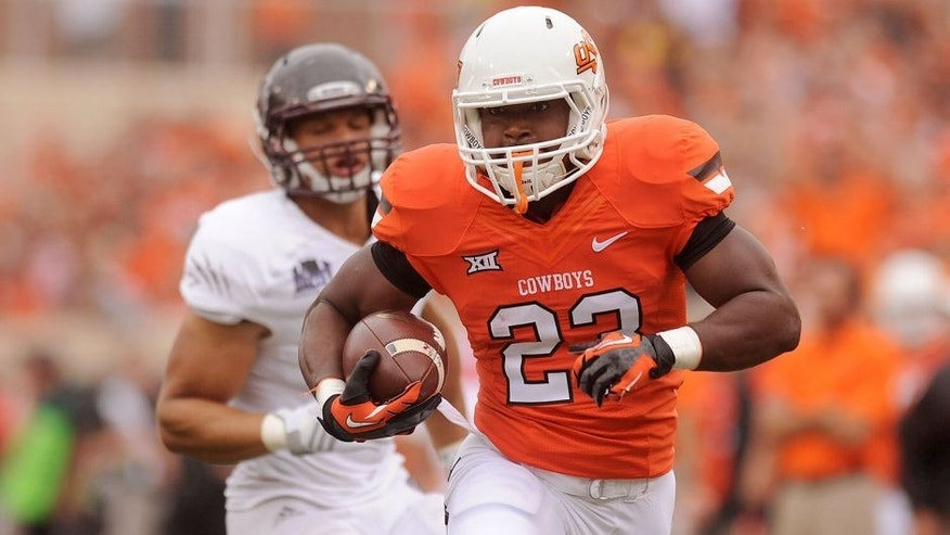 Sep 6, 2014; Stillwater, OK, USA; Oklahoma State Cowboys running back Rennie Childs (23) runs the ball against the Missouri State Bears during the first quarter at Boone Pickens Stadium. Mandatory Credit: Mark D. Smith-USA TODAY Sports