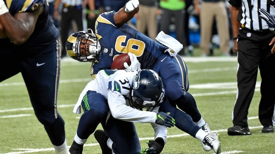 Sep 13, 2015; St. Louis, MO, USA; Seattle Seahawks free safety Dion Bailey (37) brings down St. Louis Rams running back Benny Cunningham (36) during the second half at the Edward Jones Dome. Mandatory Credit: Jasen Vinlove-USA TODAY Sports
