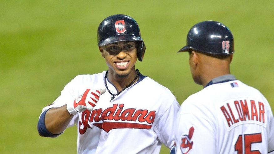 Sep 16, 2015; Cleveland, OH, USA; Cleveland Indians shortstop Francisco Lindor (12) celebrates his RBI single with first base coach Sandy Alomar Jr. (15) in the second inning against the Kansas City Royals at Progressive Field. Mandatory Credit: David Richard-USA TODAY Sports
