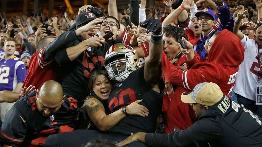 San Francisco 49ers running back Carlos Hyde celebrates with fans after scoring on a 17-yard touchdown run against the Minnesota Vikings during the second half of an NFL football game in Santa Clara, Calif., Monday, Sept. 14, 2015.
