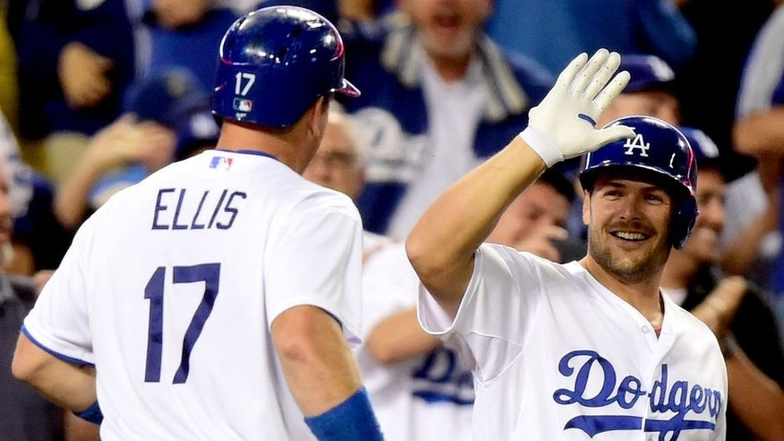 LOS ANGELES, CA - SEPTEMBER 16: A.J. Ellis #17 of the Los Angeles Dodgers celebrates his solo homerun with Chris Heisey #28 of the Los Angeles Dodgers for a 1-0 lead over the Colorado Rockies during the second inning at Dodger Stadium on September 16, 2015 in Los Angeles, California. (Photo by Harry How/Getty Images)