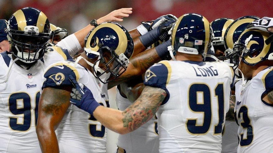 Sep 26, 2013; St. Louis, MO, USA; St. Louis Rams defensive tackle Michael Brockers (90) defensive end Robert Quinn (94) and defensive end Chris Long (91) huddle up before a game against the San Francisco 49ers at the Edward Jones Dome. Mandatory Credit: Jeff Curry-USA TODAY Sports