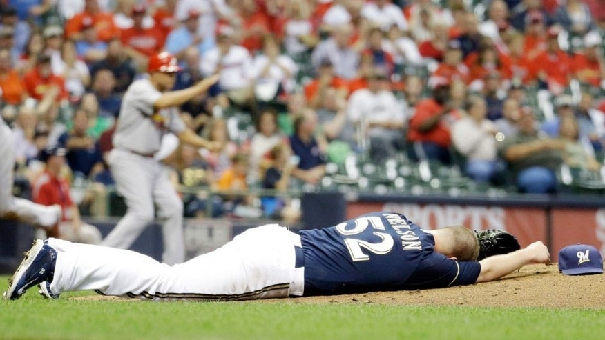 <p>Milwaukee Brewers starting pitcher Jimmy Nelson lays on the ground after being hit in the head by a ball hit by St. Louis Cardinals' Thomas Pham during the third inning of a baseball game Thursday, Sept. 17, 2015, in Milwaukee. (AP Photo/Morry Gash)</p>