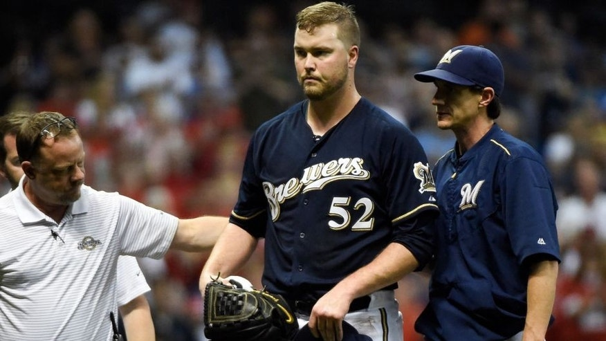 <p>Sep 17, 2015; Milwaukee, WI, USA; Milwaukee Brewers pitcher Jimmy Nelson (52) leaves the game after being hit by a line drive off the bat of St. Louis Cardinals center fielder Thomas Pham (not pictured) in the third inning at Miller Park. Mandatory Credit: Benny Sieu-USA TODAY Sports</p>