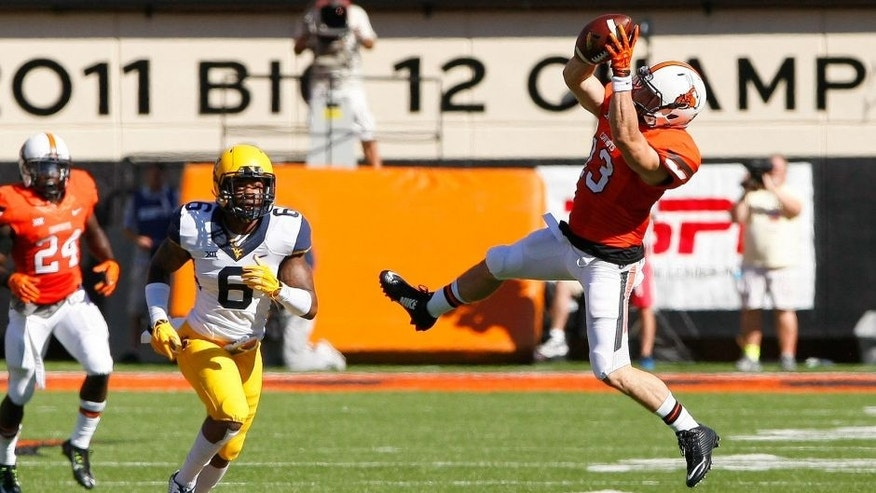 Oct 25, 2014; Stillwater, OK, USA; Oklahoma State Cowboys wide receiver David Glidden (13) goes up for a catch in front of West Virginia Mountaineers safety Dravon Henry (6) during the first quarter at Boone Pickens Stadium. Mandatory Credit: Alonzo Adams-USA TODAY Sports