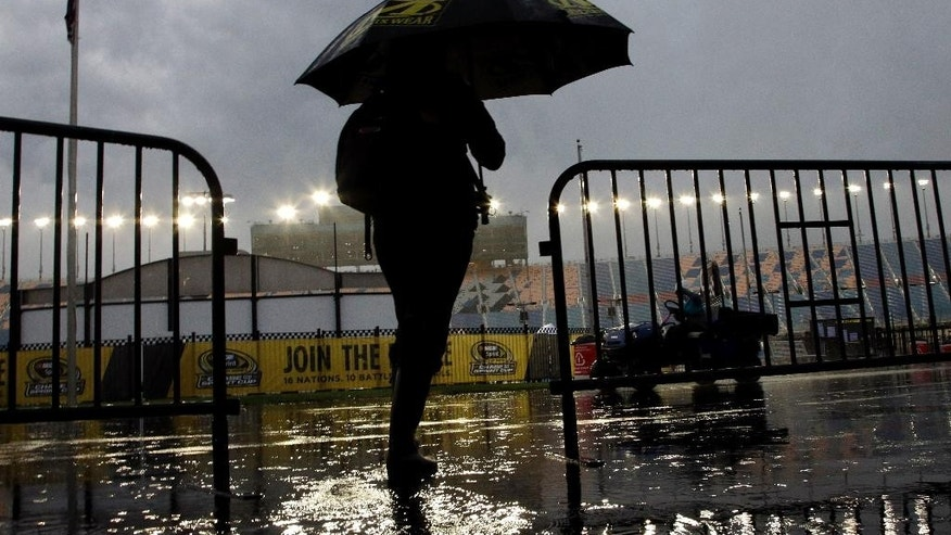 A race fan leaves during a rain delay in qualifying for the NASCAR Camping World Truck Series auto race at Chicagoland Speedway, Friday, Sept. 18, 2015, in Joliet, Ill. (AP Photo/Nam Y. Huh)