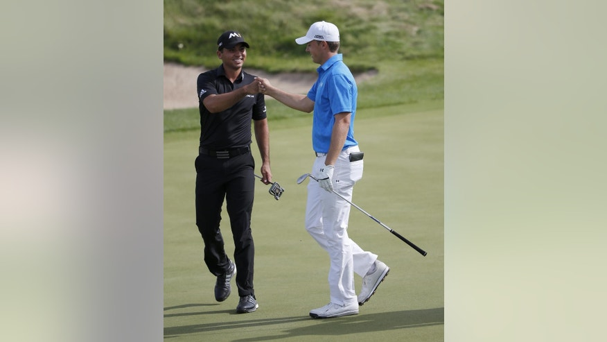 Jason Day, left, of Australia, fist bumps Jordan Spieth, after Spieth chipped in for birdie from off the green on the third hole during the first round of the BMW Championship golf tournament at Conway Farms Golf Club, Thursday, Sept. 17, 2015, in Lake Forest, Ill. (AP Photo/Charles Rex Arbogast)