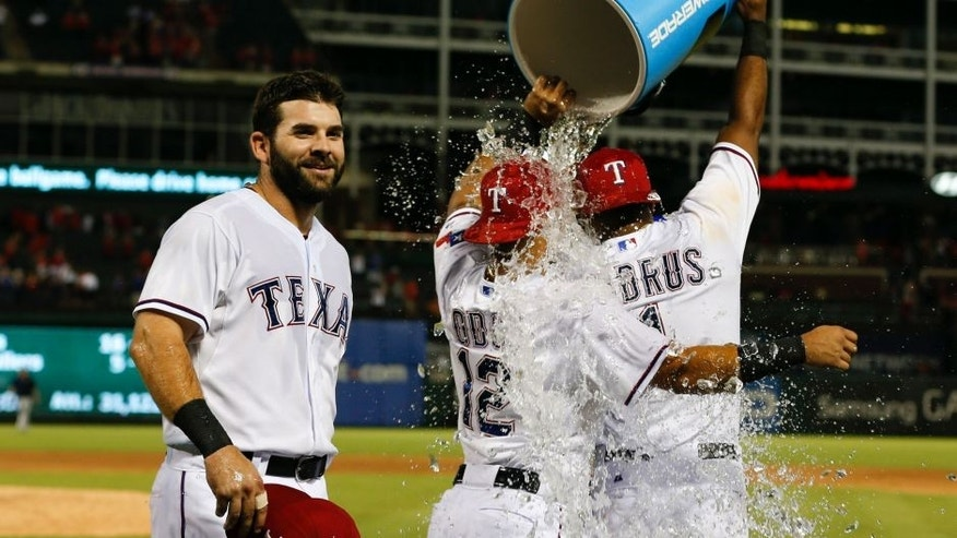 Sep 17, 2015; Arlington, TX, USA; Texas Rangers first baseman Mitch Moreland (left) and second baseman Rougned Odor (12) and shortstop Elvis Andrus (1) celebrate their win over the Houston Astros following a baseball game at Globe Life Park in Arlington. The Rangers won 8-2. Mandatory Credit: Jim Cowsert-USA TODAY Sports