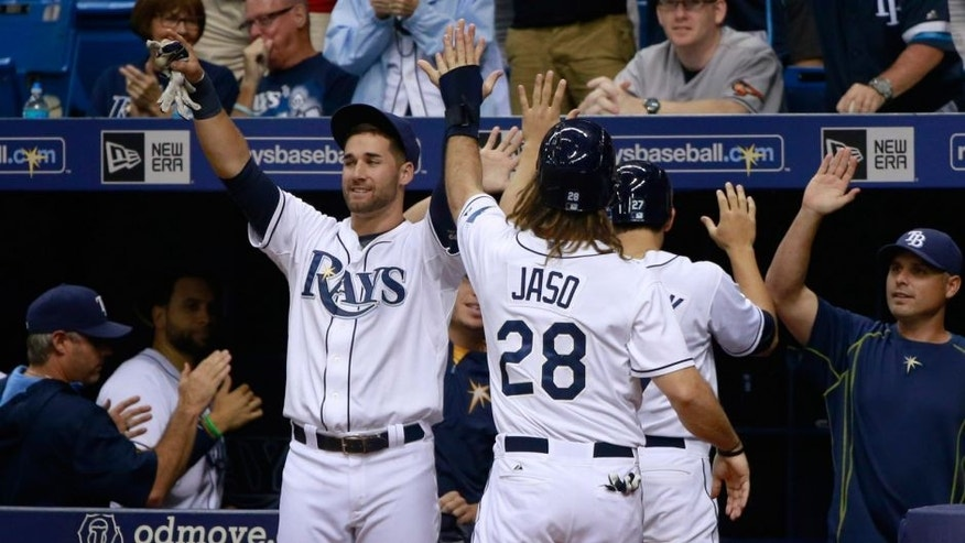 Sep 18, 2015; St. Petersburg, FL, USA; Tampa Bay Rays center fielder Mikie Mahtook (27) and designated hitter John Jaso (28) are congratulated by teammates as they scored during the fifth inning against the Baltimore Orioles and at Tropicana Field. Mandatory Credit: Kim Klement-USA TODAY Sports