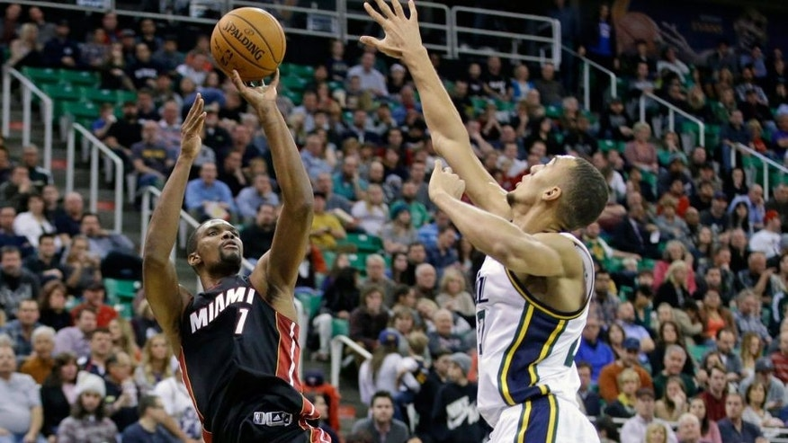Miami Heat center Chris Bosh (1) shoots as Utah Jazz center Rudy Gobert, right, defends in the second quarter during an NBA basketball game Friday, Dec. 12, 2014, in Salt Lake City. (AP Photo/Rick Bowmer)