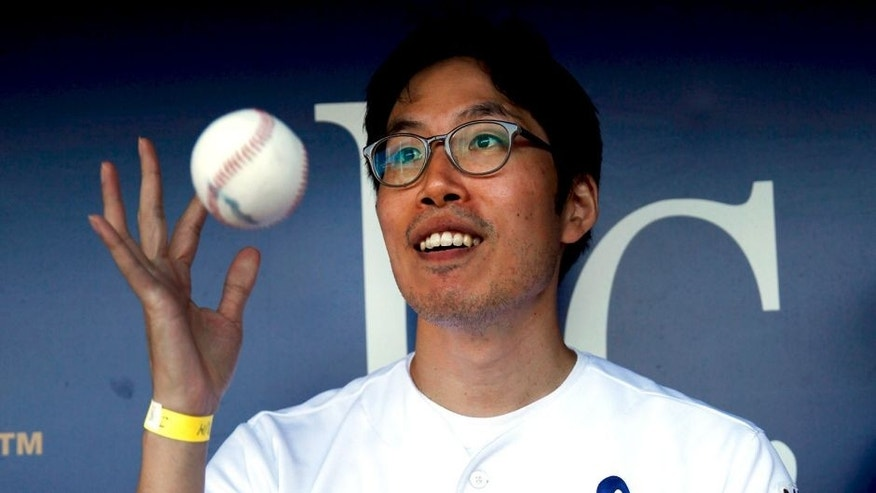 KANSAS CITY, MO - AUGUST 11: Kansas City Royals fan Sungwoo Lee of Korea shows of a signed baseball while sitting in the dugout prior to the game against the Oakland Athletics at Kauffman Stadium on August 11, 2014 in Kansas City, Missouri. (Photo by Jamie Squire/Getty Images)