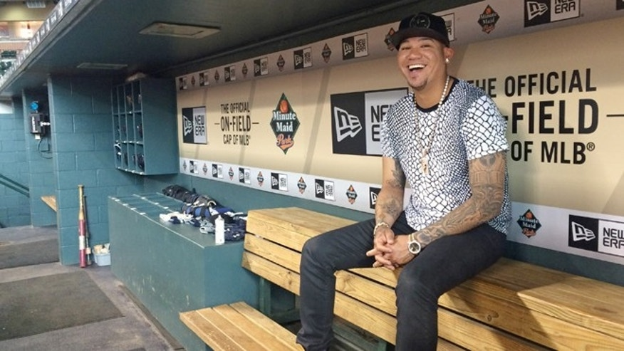 In this photo taken Tuesday, Sept. 1, 2015, Seattle Mariners ace Felix Hernández smiles as he discusses his style and love of fashion, in the visiting team dugout at Minute Maid Park in Houston. Hernández has a wardrobe befitting his royal nickname. King Felix dominates on the mound and his fashion rules off of it. The 29-year-old has painstakingly cultivated his style over 11 major league seasons and revels in discussing the intricacies of his look. (AP Photo/Kristie Rieken)
