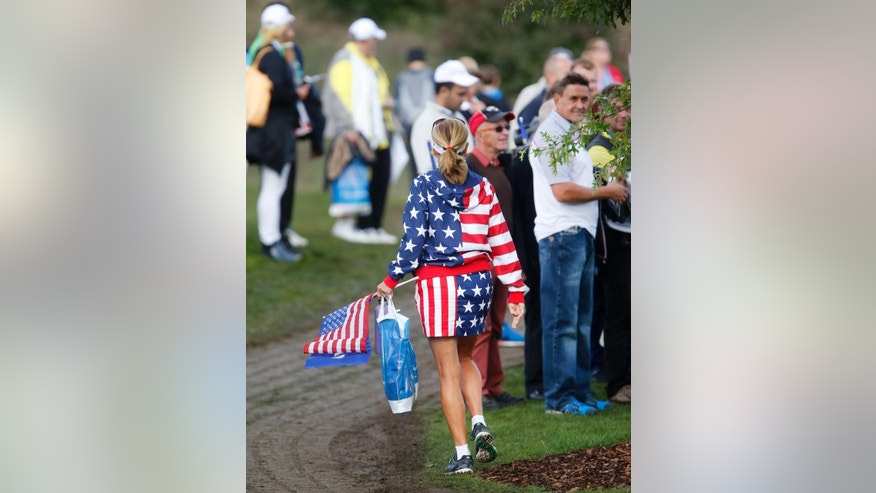 A supporter of the US team walks along the golf course on Day1 of the Golf Solheim Cup in St.Leon-Rot, Germany, Friday, Sept. 18, 2015.(AP Photo/Michael Probst)