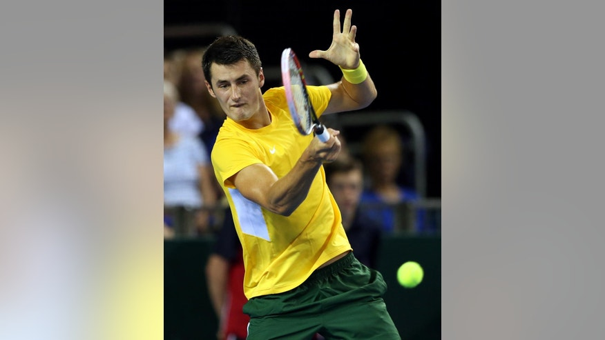 Australia's Bernard Tomic plays a return to Britain's Dan Evansduring the semifinal tennis matches of the Davis Cup in Glasgow, Friday Sept. 18, 2015. (AP Photo/Scott Heppell)