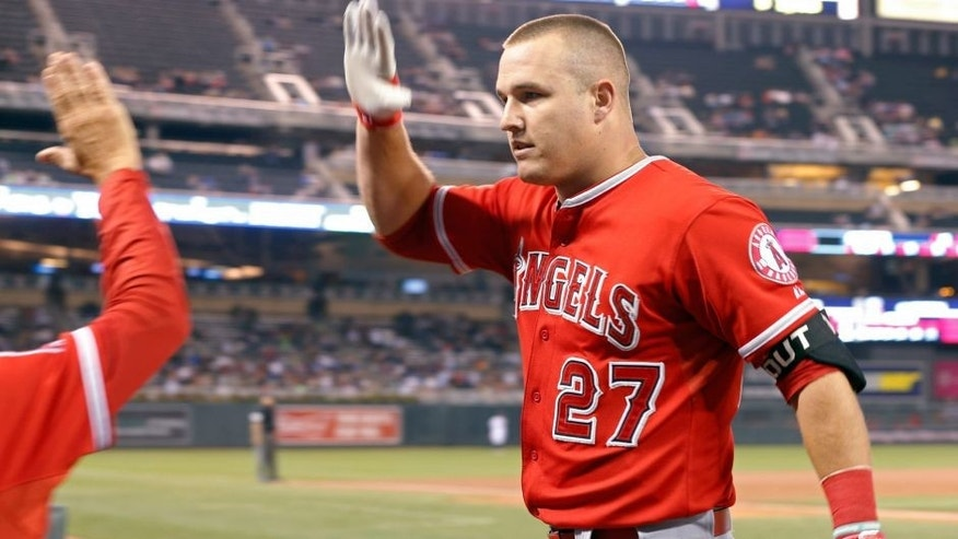 Los Angeles Angels' Mike Trout is greeted at the dugout following his grand slam off Minnesota Twins pitcher A.J. Achter during the second inning of a baseball game, Thursday, Sept. 17, 2015, in Minneapolis. (AP Photo/Jim Mone)
