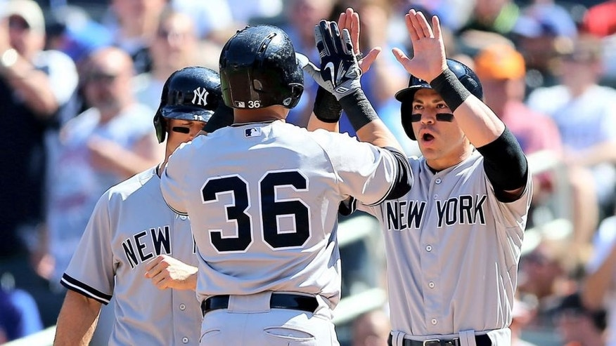 NEW YORK, NY - SEPTEMBER 19: Jacoby Ellsbury #22 and Brett Gardner #11 of the New York Yankees celebrate with Carlos Beltran #36 after Beltran drove them all in with a home run in the first inning against the New York Mets during interleague play on September 19, 2015 at Citi Field in the Flushing neighborhood of the Queens borough of New York City. (Photo by Elsa/Getty Images)