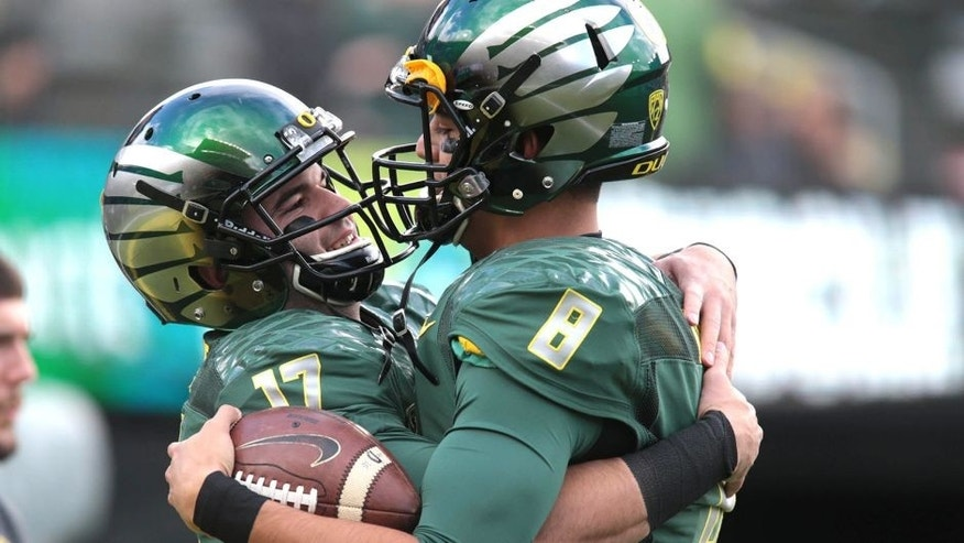 Nov 22, 2014; Eugene, OR, USA; Oregon Ducks quarterback Marcus Mariota (8) and quarterback Jeff Lockie (17) talk before the game against the Colorado Buffaloes at Autzen Stadium. Mandatory Credit: Scott Olmos-USA TODAY Sports