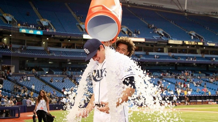 Sep 18, 2015; St. Petersburg, FL, USA; Tampa Bay Rays center fielder Mikie Mahtook (27) gets gatorade and ice dumped on him by pitcher Chris Archer (22) after he went 5-5 and beat the Baltimore Orioles at Tropicana Field. Tampa Bay Rays defeated the Baltimore Orioles 8-6. Mandatory Credit: Kim Klement-USA TODAY Sports