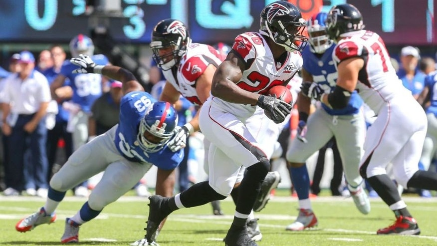 Sep 20, 2015; East Rutherford, NJ, USA; Atlanta Falcons running back Tevin Coleman (26) runs with the ball while being pursued by New York Giants defensive end George Selvie (93) during the first half at MetLife Stadium. Mandatory Credit: Ed Mulholland-USA TODAY Sports