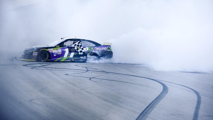 Denny Hamlin does a burnout after winning the NASCAR Sprint Cup Series auto race at Chicagoland Speedway, Sunday, Sept. 20, 2015, in Joliet, Ill. (AP Photo/Matt Marton)